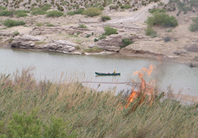 A firefighter in a canoe on the river observes fire on the riverbank.