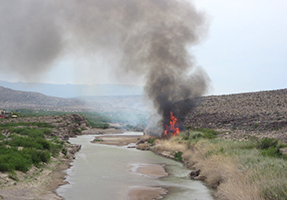 River, large flames on riverbank, and small nearby community.