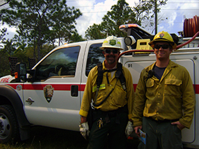 Two firefighters stand near a wildland fire engine.