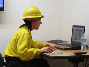 A firefighter in Nomex flame-resistant gear sits in front of a computer at a desk.