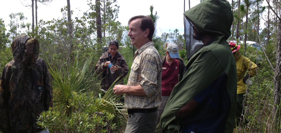 Three people stand talking in an open area near vegetation and pine trees.