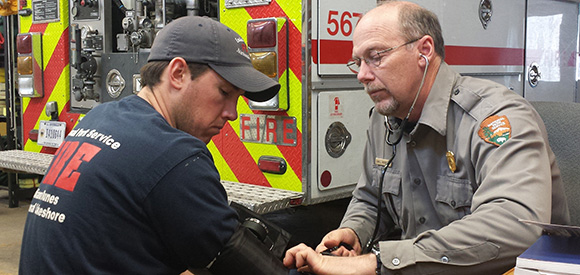 A man in a National Park Service uniform uses a blood pressure cuff on another man.