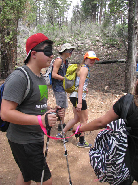 A blind folded, sighted student is led on the trail during a Leading the Way exercise.