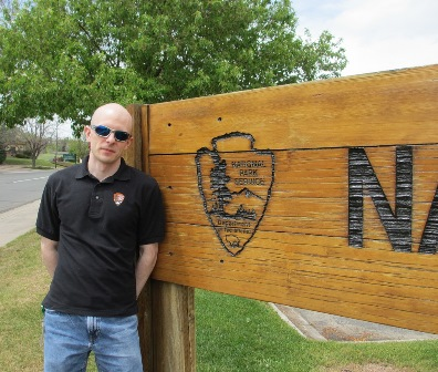 NPS Employee Charles Notzon standing next to a wooden NPS sign