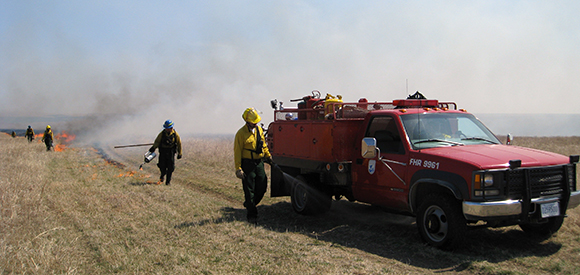 A firefighter walks near a wildland fire engine while a fire burns in grass in the distance.