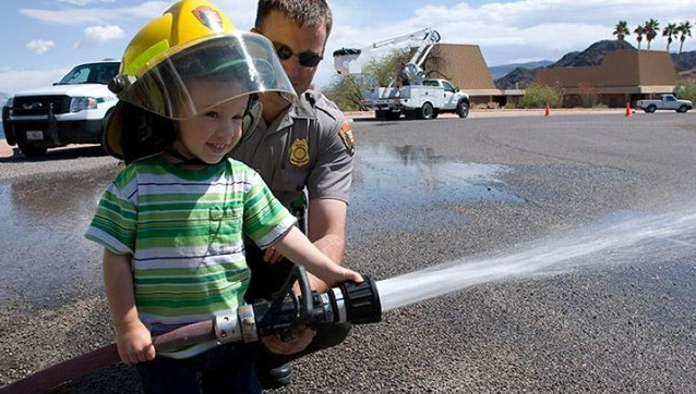 young boy holds a fire hose for the first time.