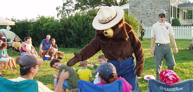 smokey bear shaking hands with the public at a backyard BBQ