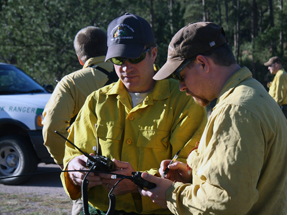 two firefighters track and maintain radios on an fire incident.