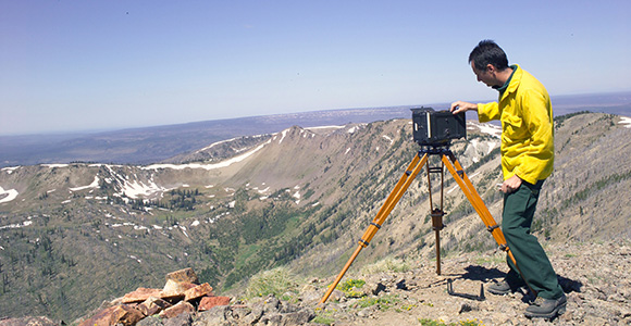 Ian Grob adjusts an Osborne photo recording transit looking out over mountain and valley.