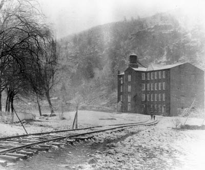 A black and white image of railroad spur leading toward a four-story brick mill building.