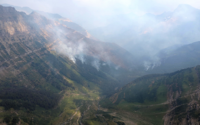 Smoke rising from steep mountainous valley.
