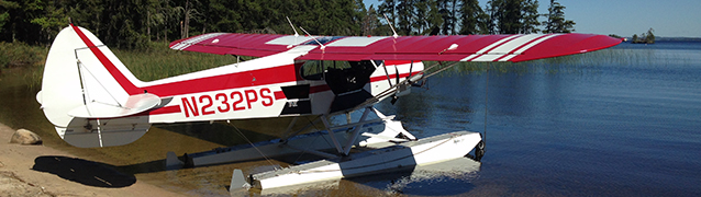 A fixed wing airplane of floats sits on the shore of a lake.