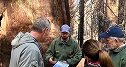 A National Park Service employee speaks to two men and a woman.