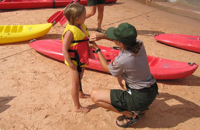 NPS Ranger helping a young child put on a properly fitted U.S. Coast Guard approved life jacket