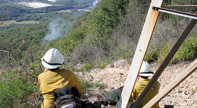 Two firefighters sit on a ridgetop overlooking a forested slope and smoke column.