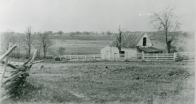 Historic image of an agricultural landscape with farm buildings, fencing, and fields.