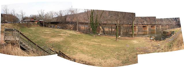 Stitched panorama shows a wide view of a level, grassy area between a berm and the river.