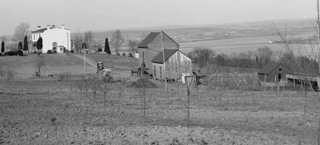 A distant view of a two-story farm house surrounded by fields, farm buildings, and expansive views.