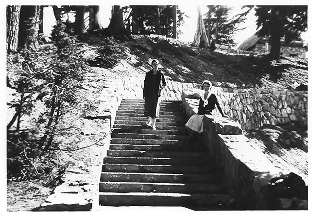 Two women on a wide stone stairway, one seated on the stone wall and one standing.