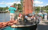 A sloop boat prepares to sail away from the dock.