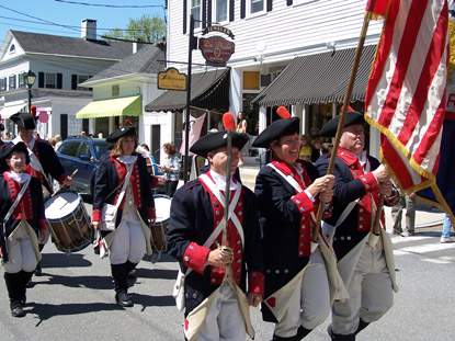 War of 1812 reinactors march down a main street holding flag