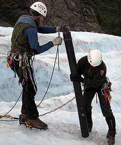 Two scientists taking an ice core from a glacier