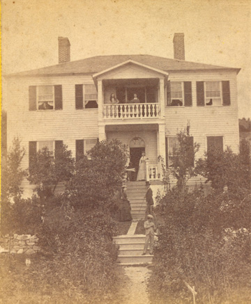 Photograph of a house with an American Indian entrepreneur standing on porch