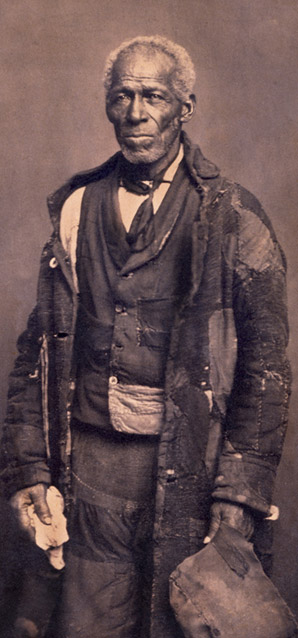 Photograph of sailor George Roberts, wearing tattered clothes