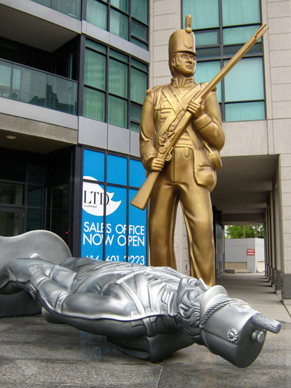Statue of gold and fallen silver toy soldiers