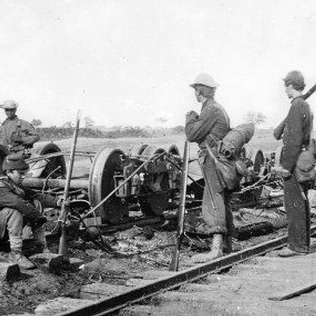 Three Union soldiers and one African-American civilian pause over a collection of railroad trucks on the Orange and Alexandria Rail Road line.