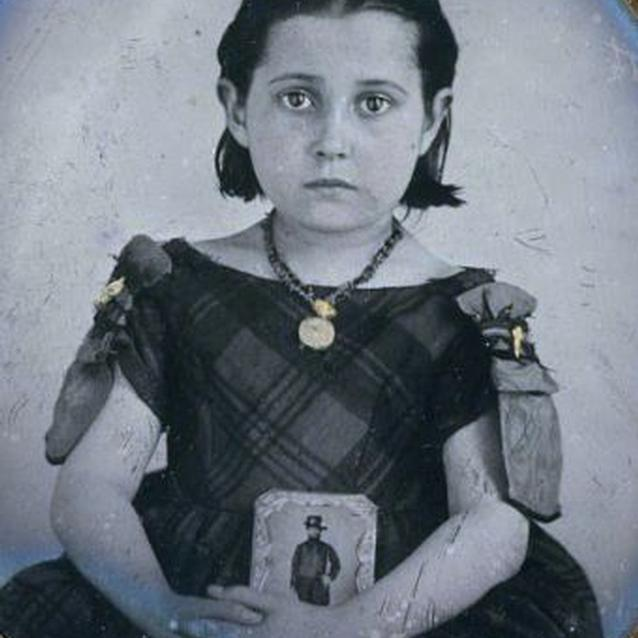 Photo of a young girl in mourning dress with a photograph of her cavalryman father