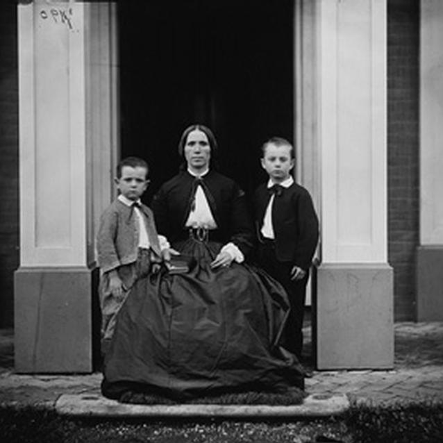 Photograph of two children with their mother outside their home