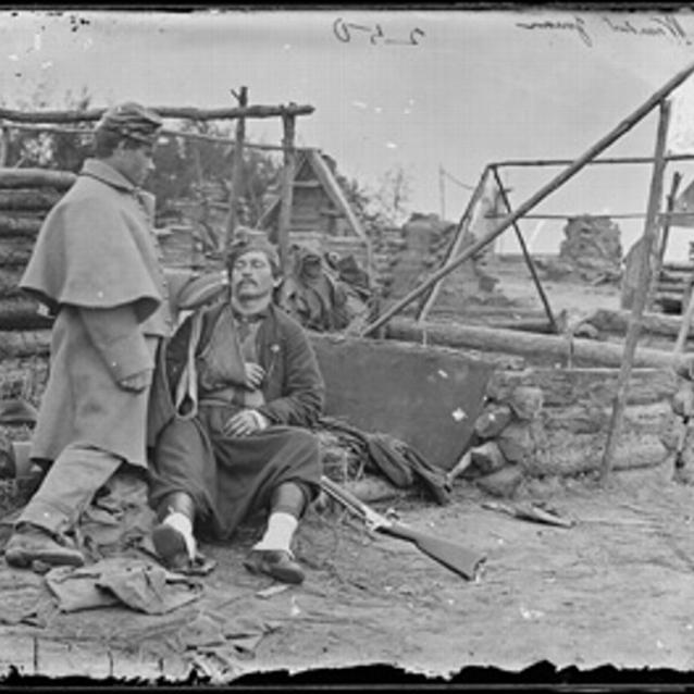 Photograph of two soldiers, one wounded