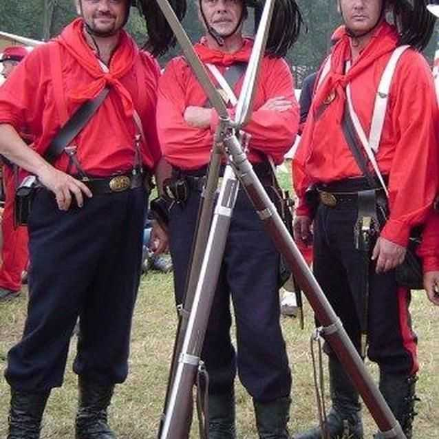 Photo of Garibaldi Guard living historians, in red shirts with black plumed hats.