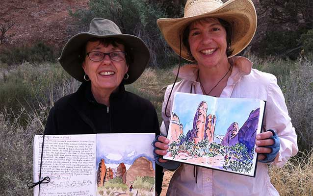 two women hold up watercolor paintings