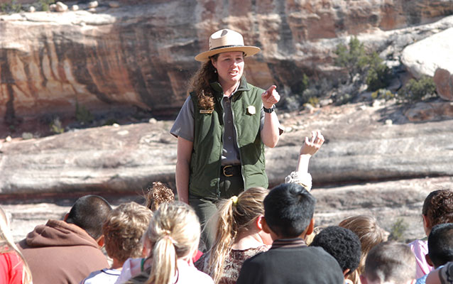 A park ranger stands in front of a group of students