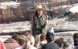 A park ranger stands in front of a group of students.