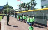 superintendent swearing in group of junior rangers with their hands raised in front of a baseball scoreboard
