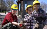 Two youngsters learn about a fire hose with a park firefighter.