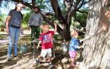 young children throw mud on ocotillo test wall while ranger and parent look on