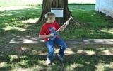 Boy playing cigar box guitar.