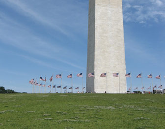 American flags form a ring around the base of the Washington Monument obelisk.