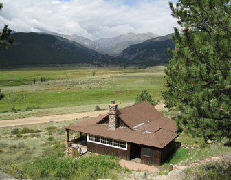 A view includes the top of a one story cabin, a wide flat plain, and dramatic mountains beyond.