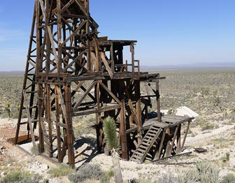 The angular wooden headframe of a mine stand out on the flat expanse of desert.
