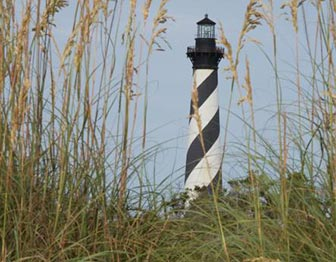 The black and white stripes of Cape Hatteras Lighthouse are seen through a stand of sea oats.