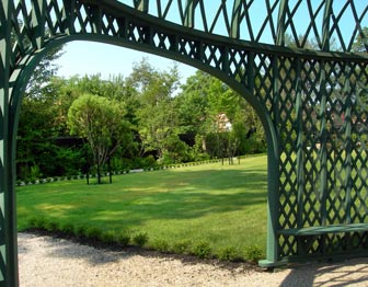 The view out from under a green framework of a pergola, with green lawn