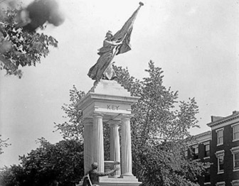 Black & white photograph of stone memorial with female figure holding flag. Key is craved in stone.