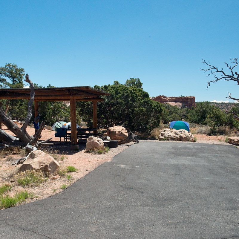 a paved driveway with a shade structure and two tents in the background
