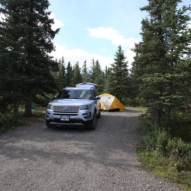 an SUV parked in a forest with a tent behind it