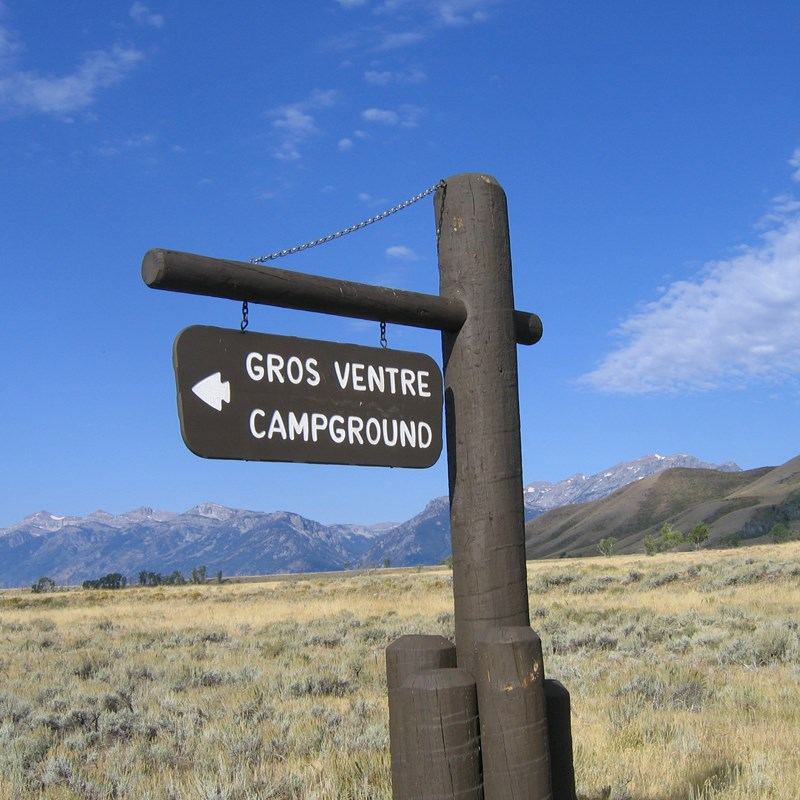 Entrance sign for Gros Ventre Campground with Blacktail Butte and the Teton Range in the distance.